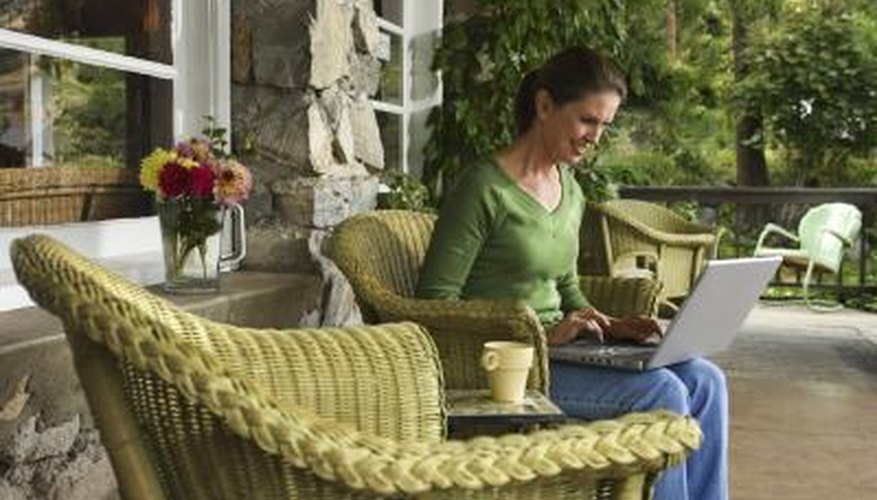 Woman sitting on patio furniture outside on deck