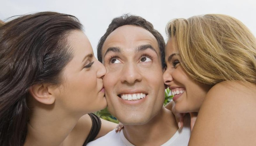 A man smiling while being kissed on the cheeks by two ladies.