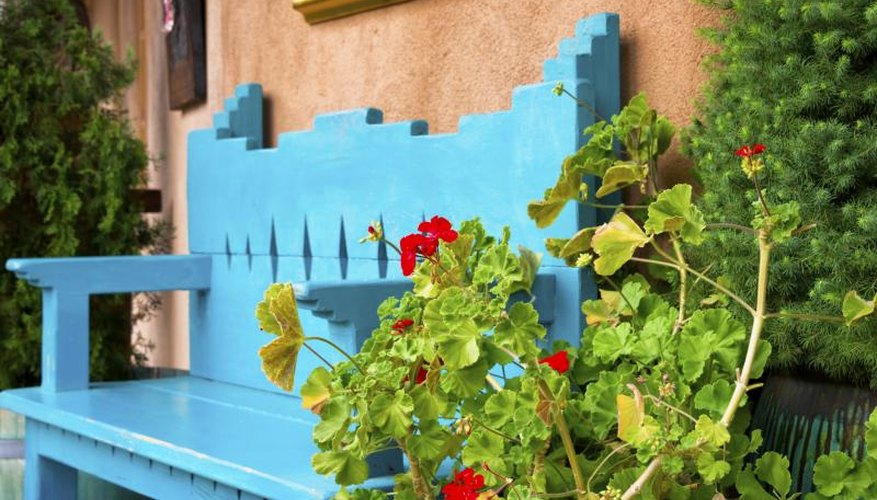 A hand-painted wooden bench in front of a stucco wall nestling between flowering shrubs.