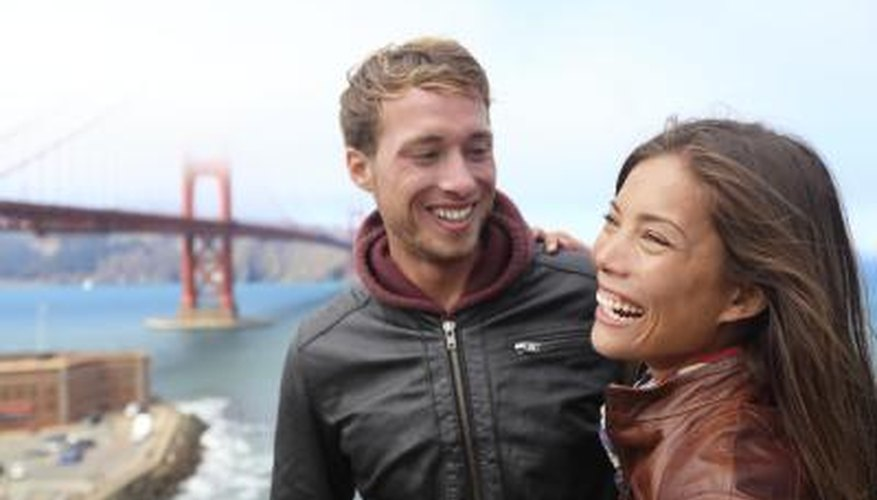 A man and woman laugh together in a scenic spot by the water.