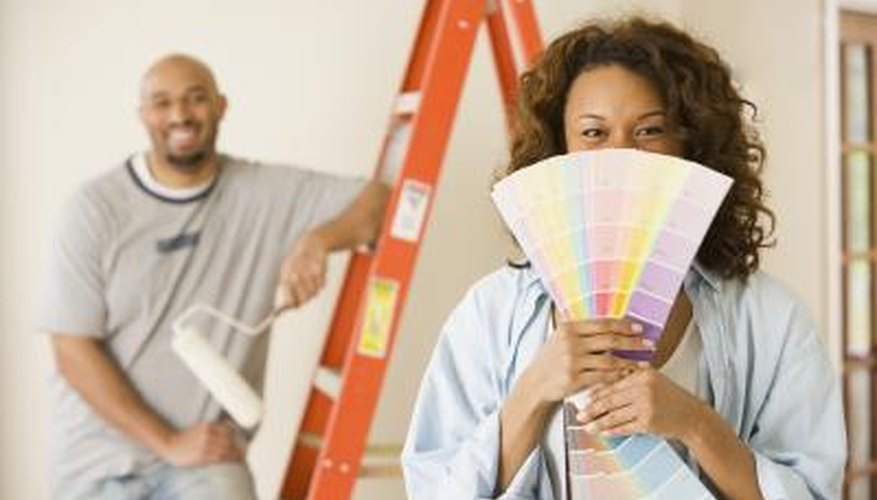 Woman holding paint swatches in front of her husband
