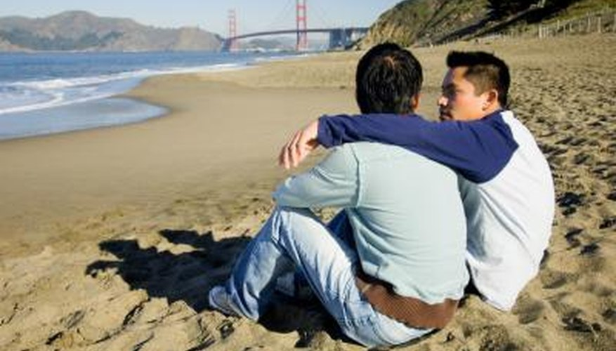 A couple sitting on a beach together in San Francisco.