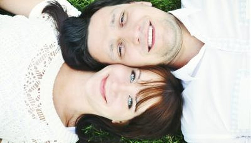 A high-angle view of a happy couple lying in the grass together.