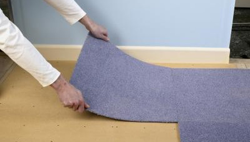 A man installs carpet