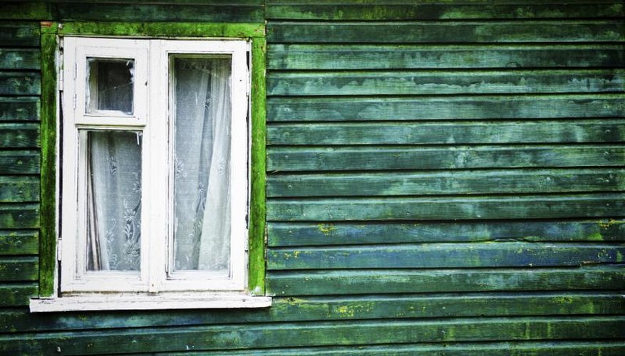 Old fashioned cottage window on green building.