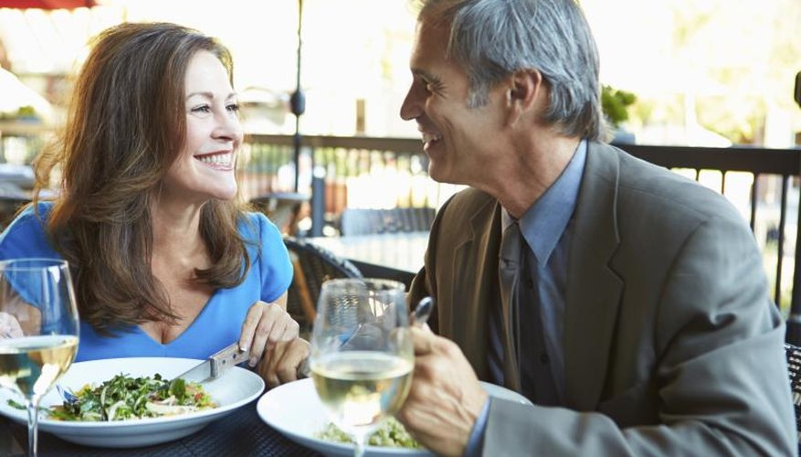 Couple on a date eating salad and drinking wine.
