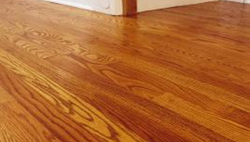 Remove adhesive from wood floors with products that are safe for urethane finishes.
