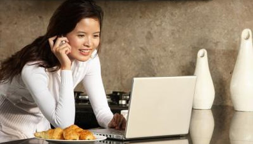 Woman making phone call while researching on laptop.