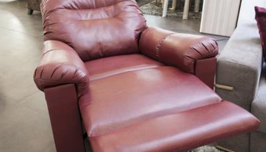 Red leather chaise recliner with elongated seat in a furniture store.