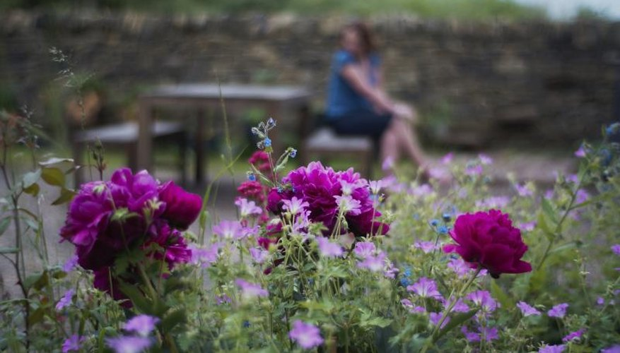 A woman sitting in a cottage garden with purple and blue forget me nots and peonies in the foreground.