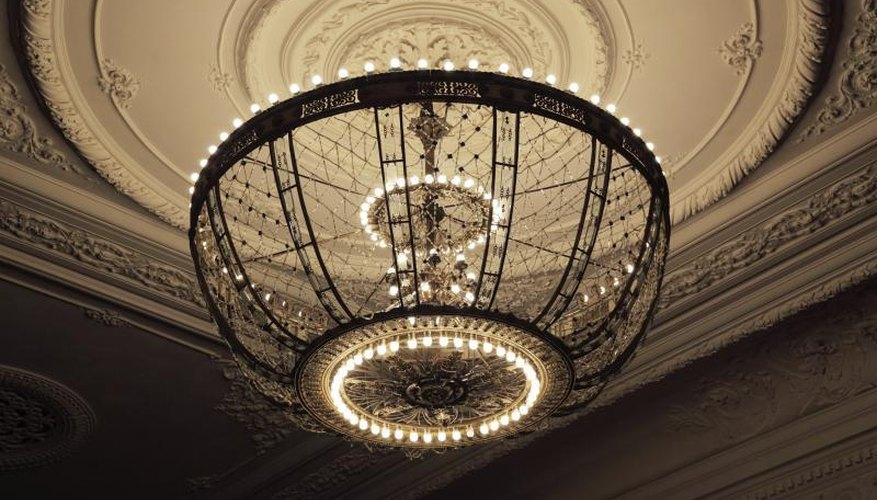 Chandelier hanging from large ornamental ceiling medallion.