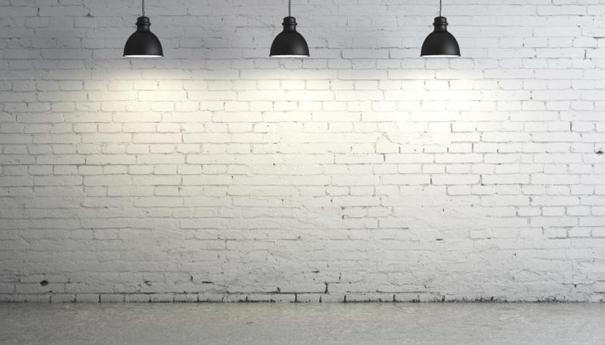 Lights against a brick wall shining on concrete floor