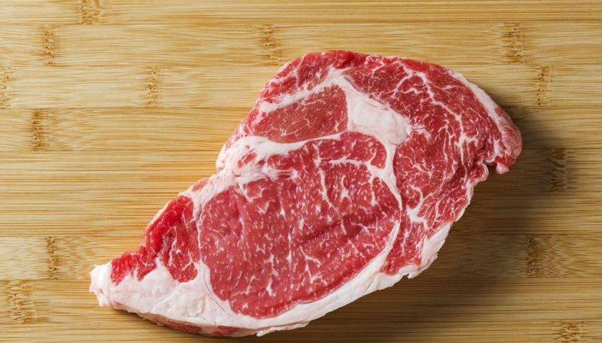 Rib eye steak on a bamboo cutting board.