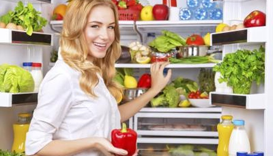 Image of a woman standing by an open refrigerator.