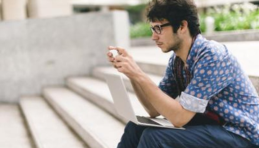 Student sitting on university steps with laptop and smart phone