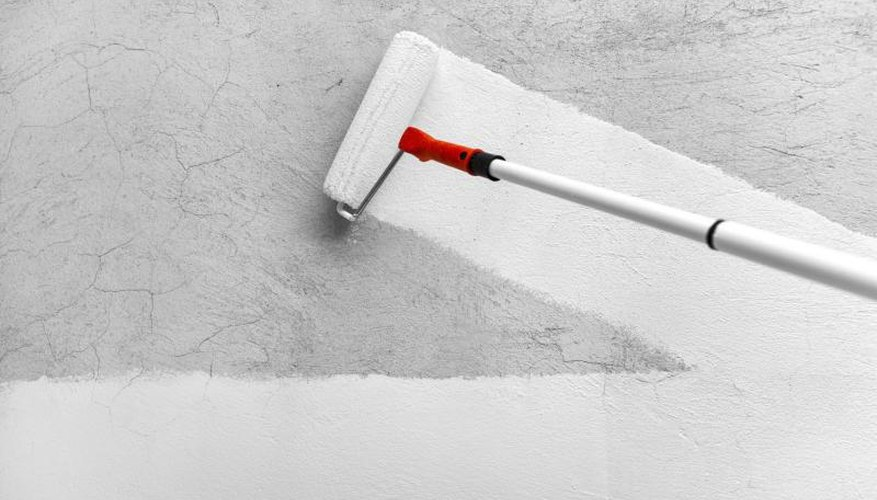 Roller spreading white paint on a gray wall