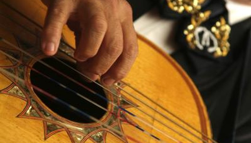A close-up of a man playing a Spanish guitar.