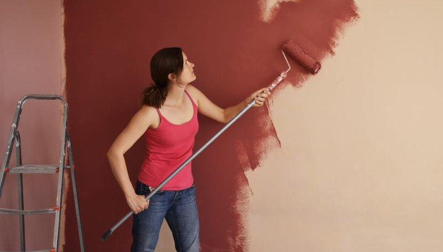 Woman using roller to paint wall