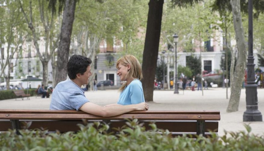 Couple talking on park bench.