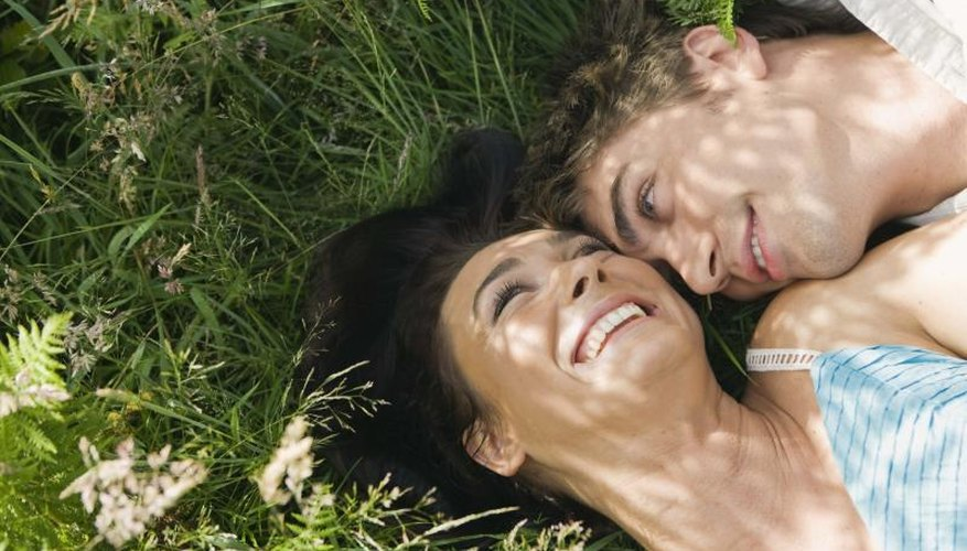 A close-up of a couple laying in a field together in the summer.