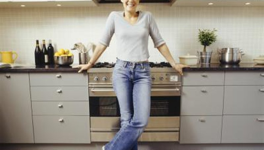A happy woman stands in her kitchen.