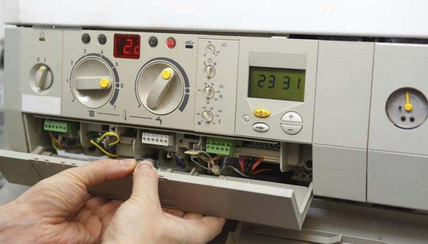 Hands removing the control panel of a gas furnace.