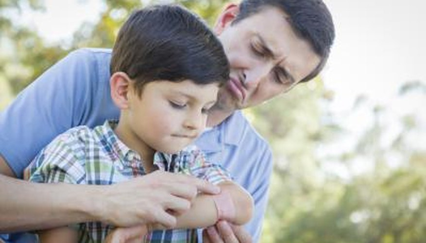 Adult helping child apply bandaid