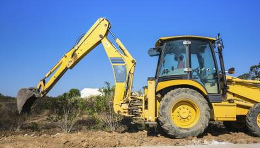A backhoe can dig a pool hole quickly but needs a lot of space to operate.