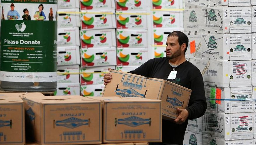 A worker stacks boxes of donated produce.
