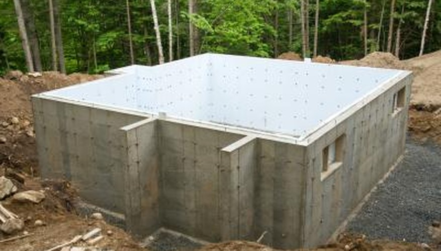 A concrete foundation wall with the first floor complete is ready for backfilling.
