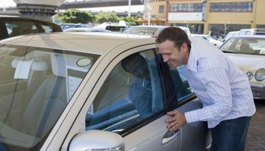 Image of a man looking at a car window.