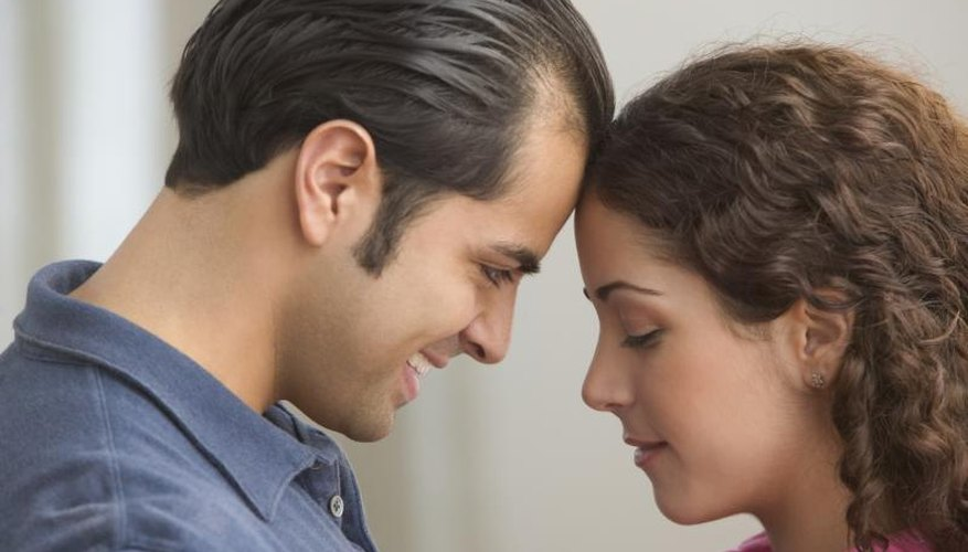 Young couple with foreheads together.