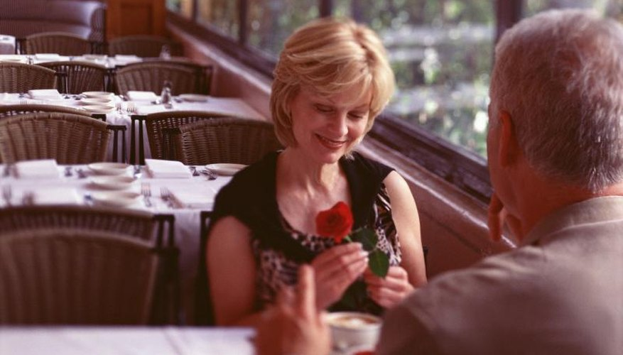 A woman receiving a rose from her date in a restaurant.