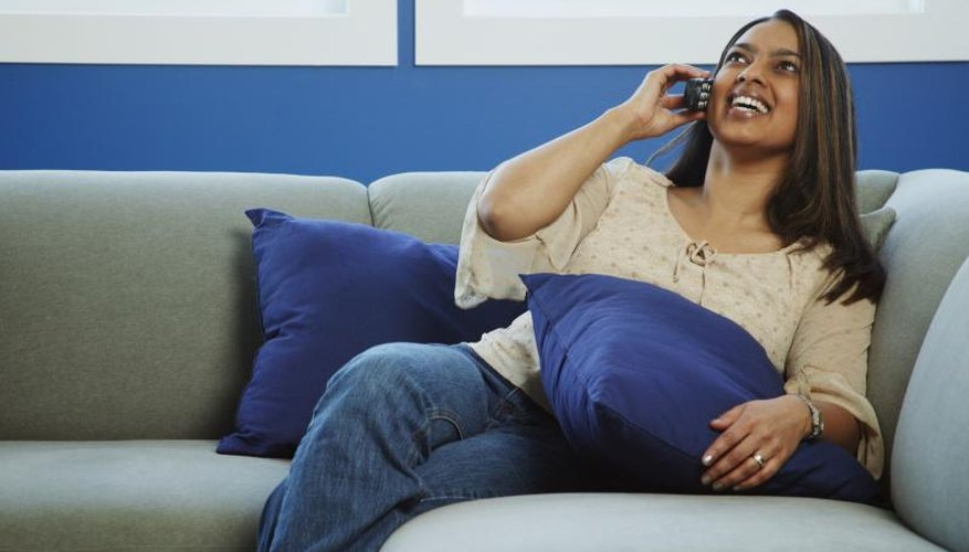 Woman talking on phone while sitting on couch.