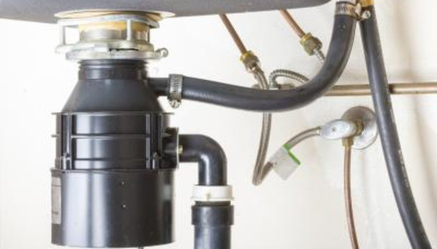 A under-sink view of a garbage disposal.