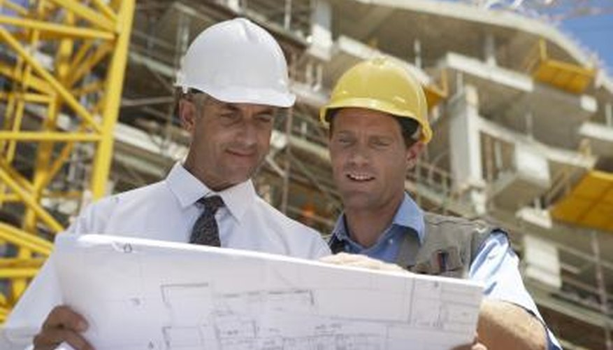 Two construction workers looking at blue prints