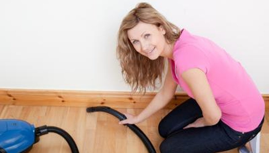 Young woman vacuums