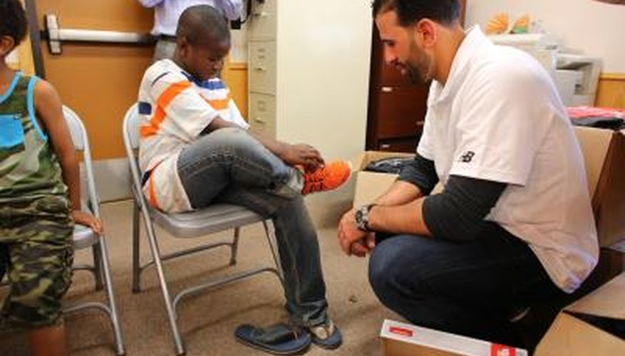 Volunteer giving shoes to child in the Boys and Girls Clubs of America.