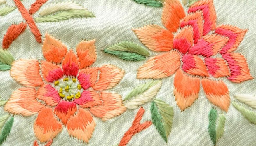 A close-up of pink and peach embroidered flowers.