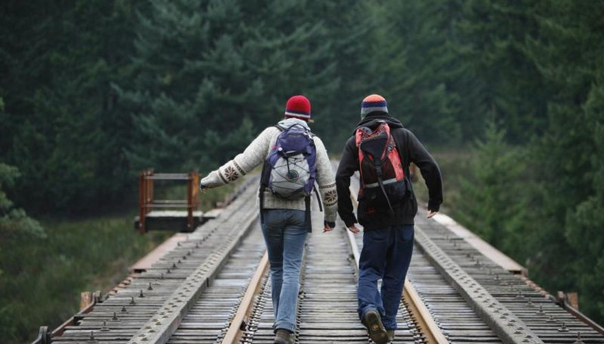 Two people hiking along a wooden rail road track.