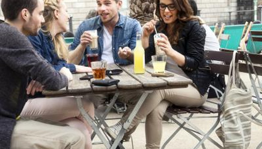 Two couples socialize at an outside cafe.