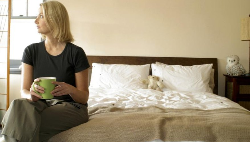 A reflective woman sitting alone on a bed with a mug.