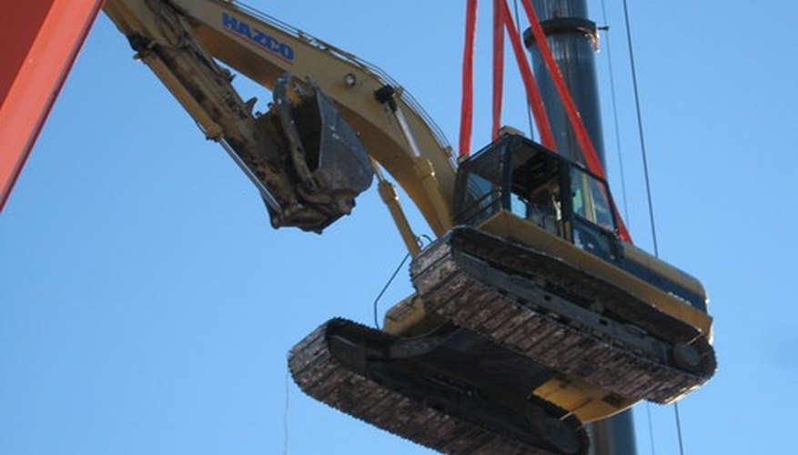 A crane lifts a digger, both of which are considered material handling equipment.