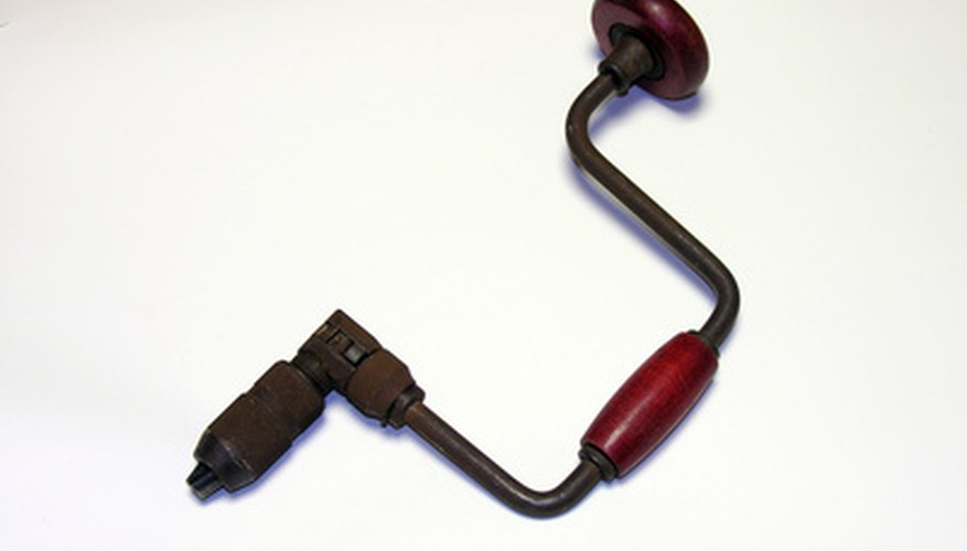Antique hand drill with wooden crank.