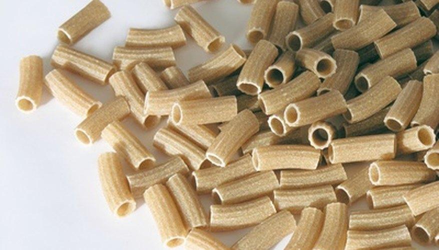 Haz collares de fideos con diferentes tipos de pasta cruda.