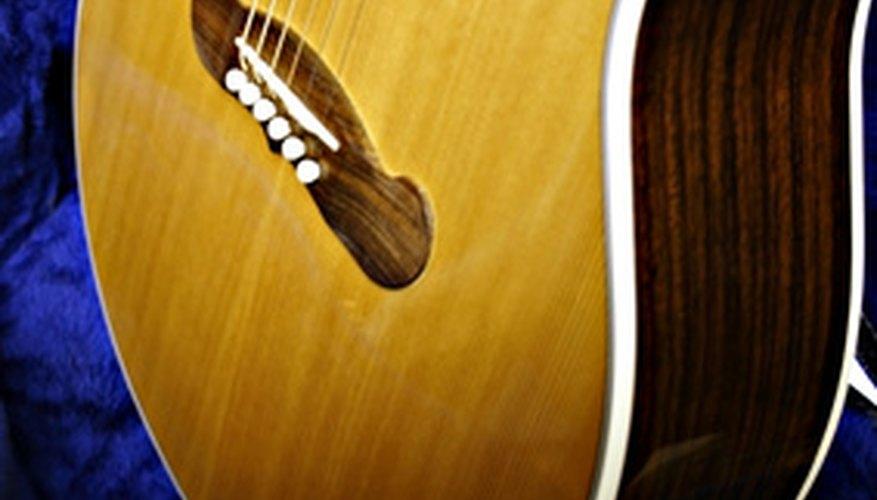 El puente de una guitarra acústica tiene clavijas que sostienen las cuerdas en su lugar.