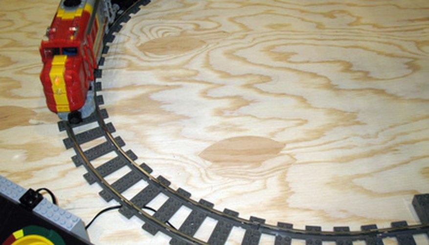 Une las vías dle tren con un destornillador y con tornillos.