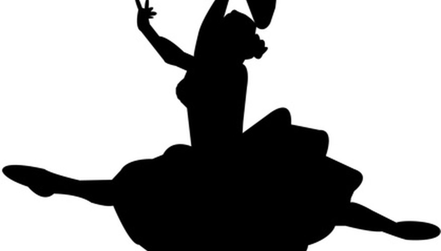 Dancer in silhouette performing a grande jeté
