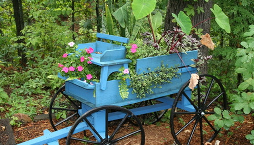 A little blue wagon that is being used for a gardening stand, showing the tongue, wheels, seat and box.