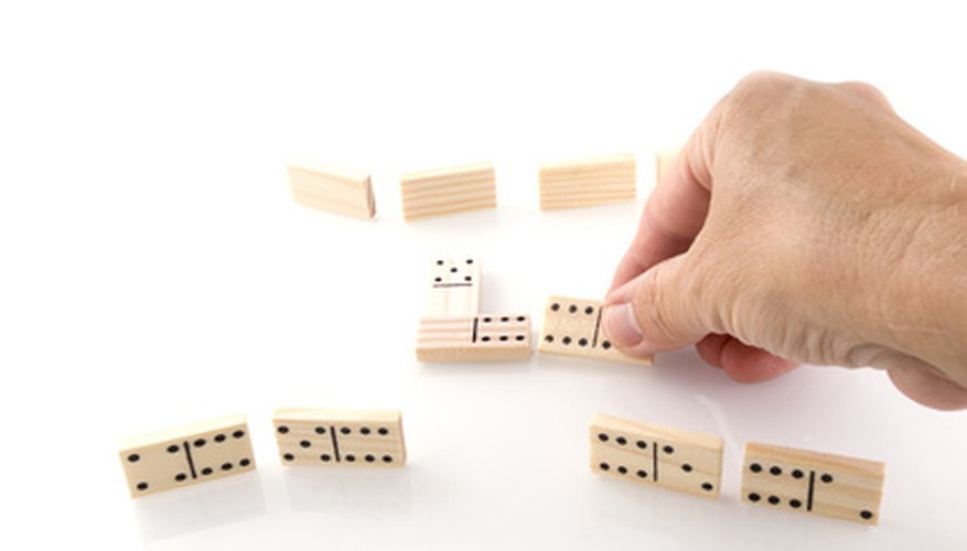 Standing domino tiles are easily knocked over if not secured in a stand.